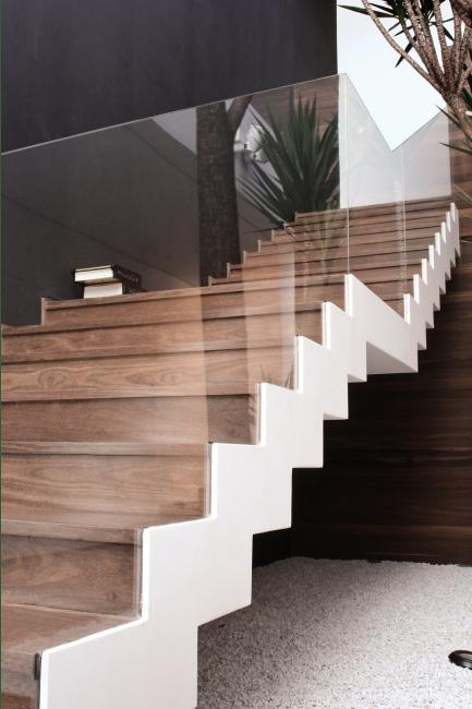 Penerbangan tangga dipisahkan secara visual dari ruang tamu dengan kaca yang jelas.