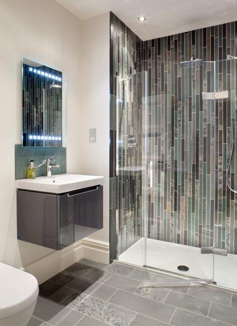 Mosaik dengan jubin bujur dalam reka bentuk menegak akan membantu untuk memperluaskan ruang secara visual ke atas.