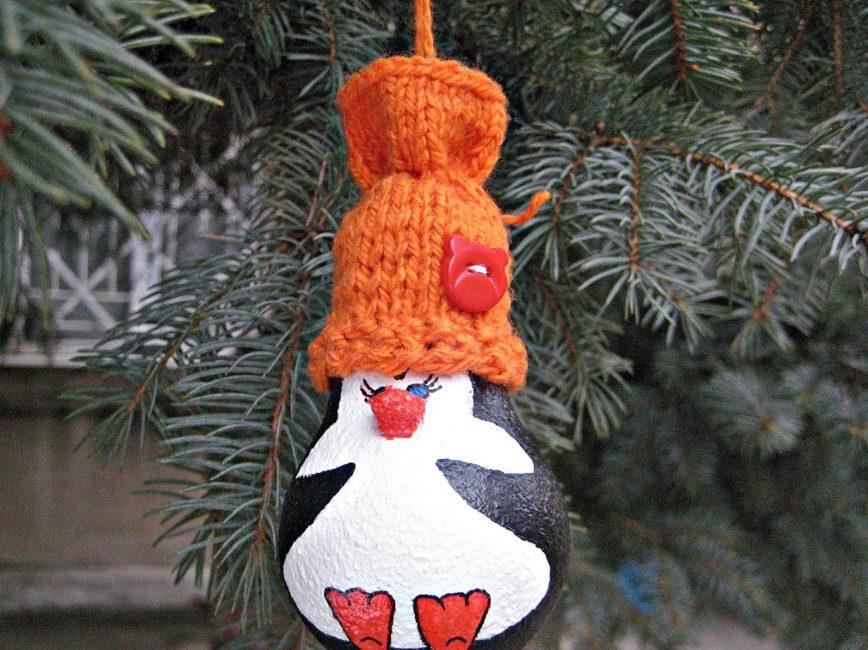 Bir Noel ağacı üzerinde bir ampul gelen harika bir penguen