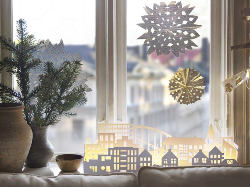 Bayang-bayang kota Tahun Baru, dipotong daripada kertas, akan kelihatan selesa jika diletakkan di dalam lilin