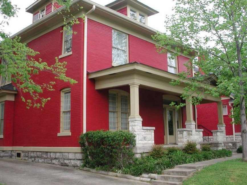 Dindingnya dicat dengan warna merah yang kaya, dan tiang beige kelihatan elegan