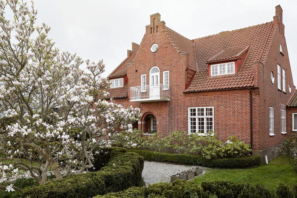 Duvarlar ve çatı aynı renktedir ve pencerelerde ve balkonda zıt beyaz